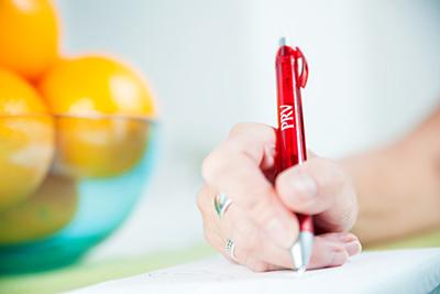 En hand skriver på ett papper med en röd penna